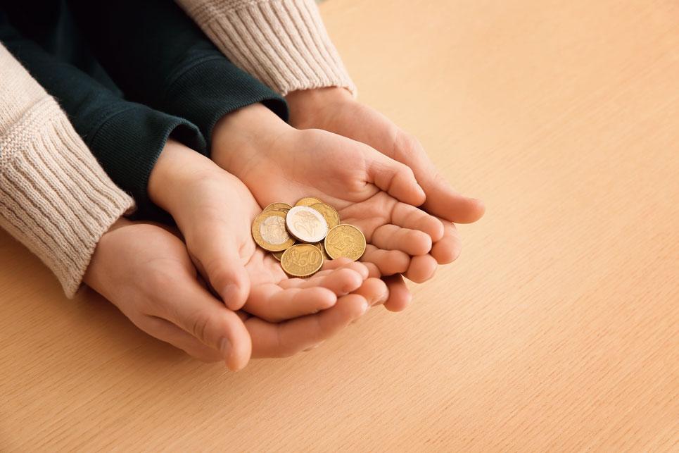 Erwachsenen- und Kinderhände mit Münzen