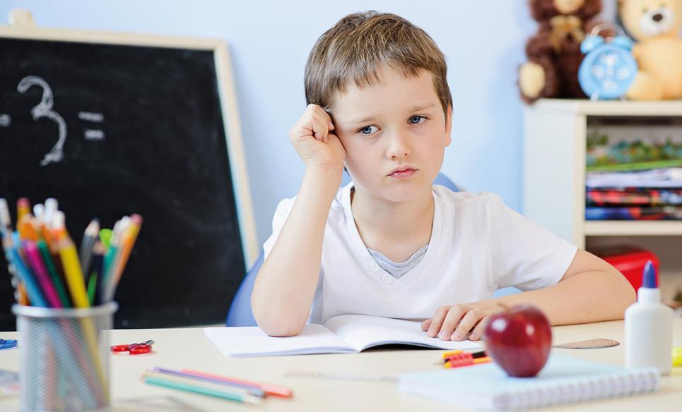 Nachdenklicher Junge sitzt am Schreibtisch