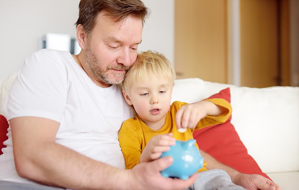 Vater und Sohn werfen gemeinsam Geld in ein Sparschwein