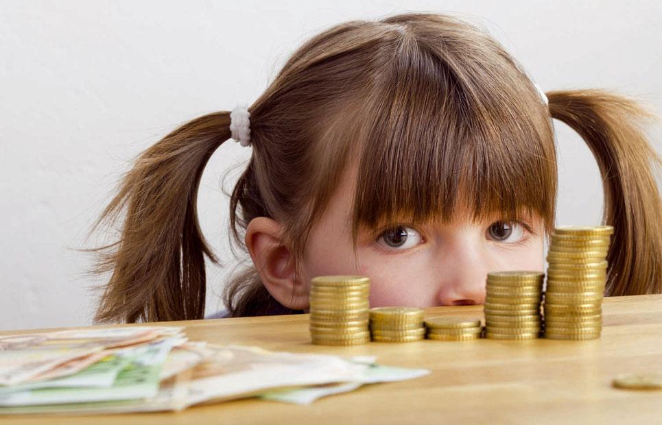 Mädchen lugt über eine Tischkante. Auf dem Tisch liegen Geldscheine und Münzen