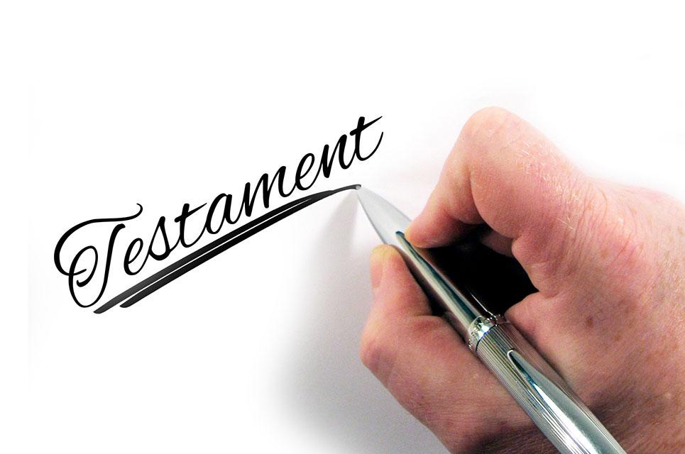 Hand mit Füller die das Wort Testament auf weißen Untergrund schreibt