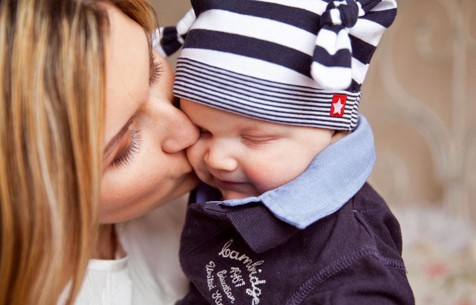 Mama küsst Baby auf die Wange