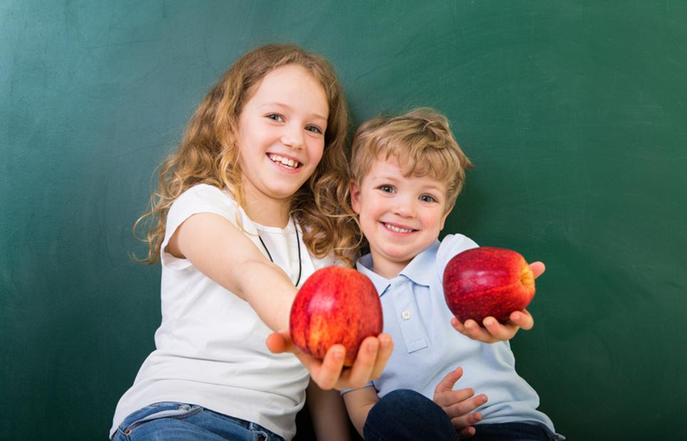 Schulkinder mit Äpfeln