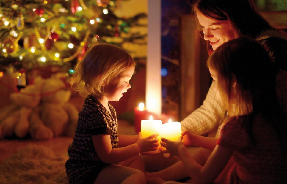Mutter mit Kindern vor dem Weihnachtsbaum