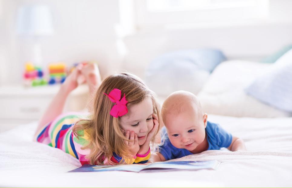 Schwester betrachtet gemeinsam mit Baby ein Bilderbuch.