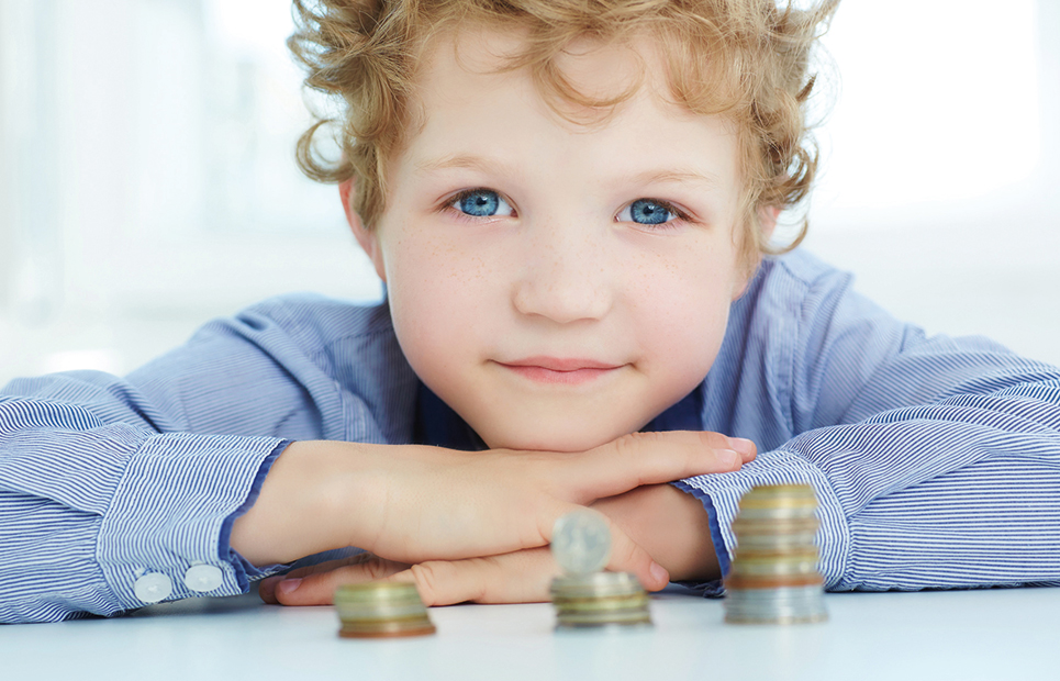 Junge sitzt hinter drei Münzstapeln.