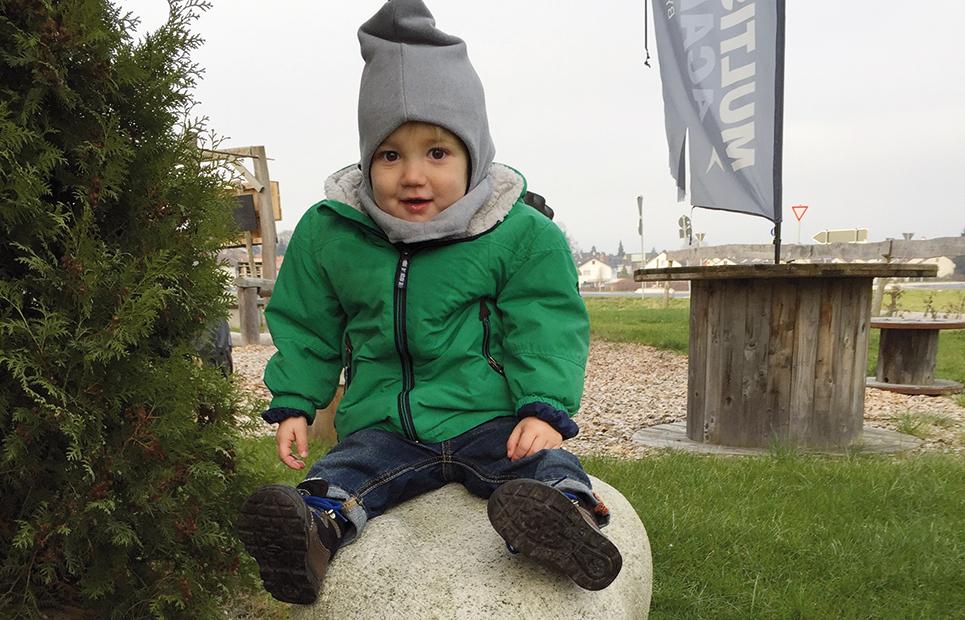 Kind sitzt auf Steinfigur