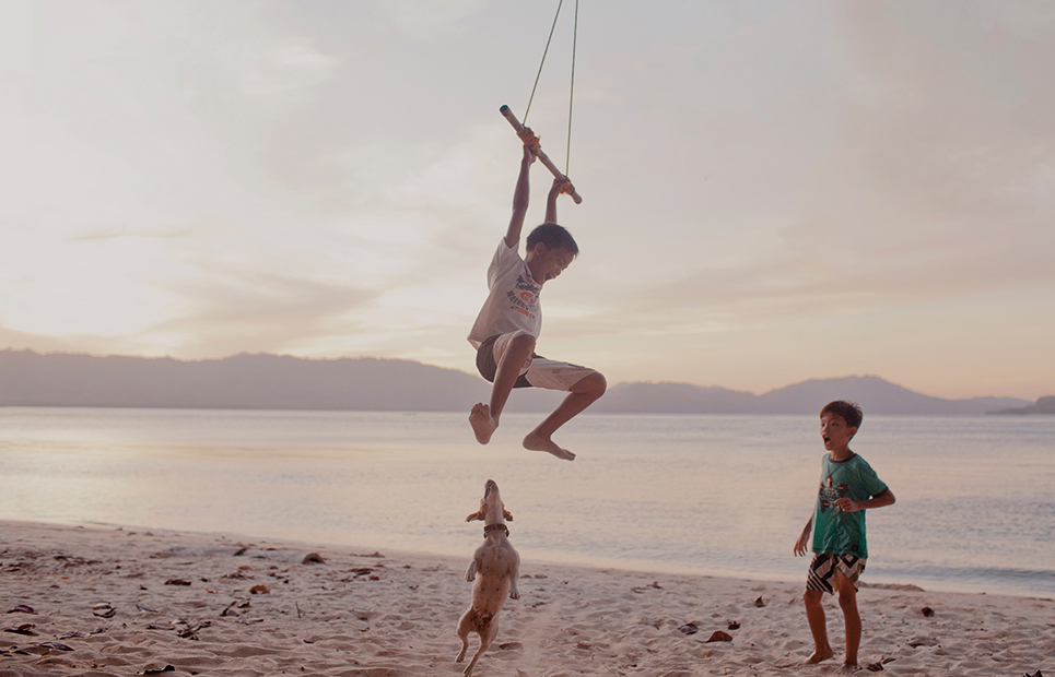 Zwei Kinder spielen mti einem Drachen und einem Hund am Strand.