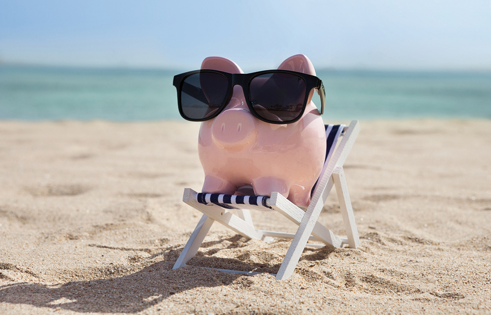 Sparschwein mit Sonnenbrille und Liegestuhl am Strand