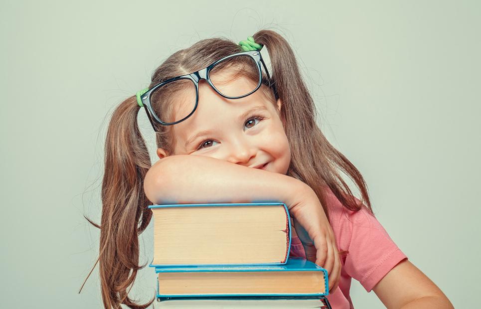 Lächelndes Mädchen stützt sich auf Bücherstapel