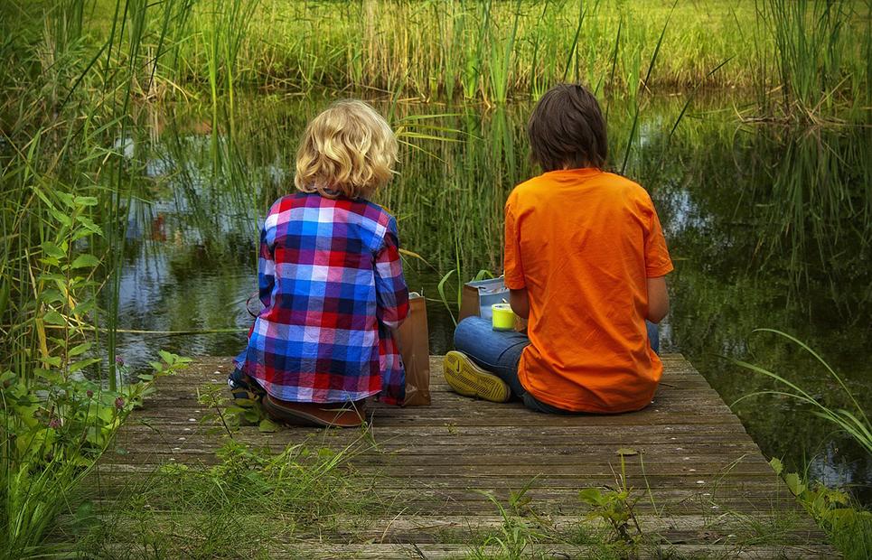zwei Freunde sitzen am Teich