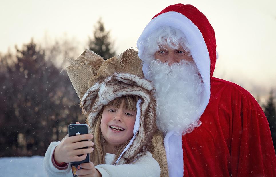 Mädchen macht Selfie mit Weihnachtsmann