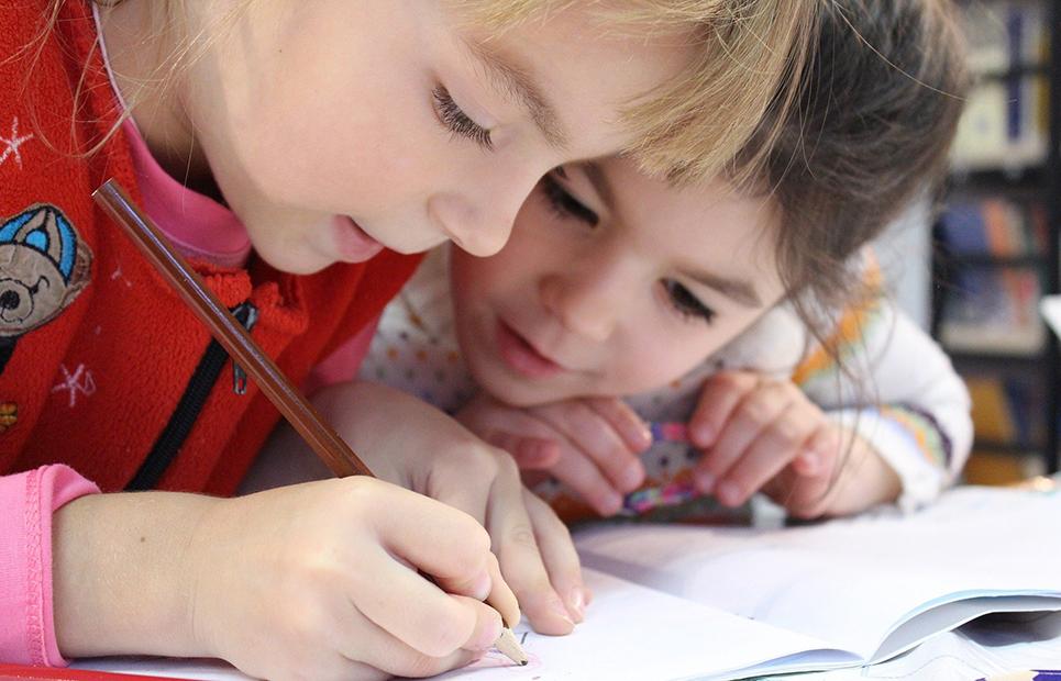 Kinder lösen gemeinsam Aufgaben