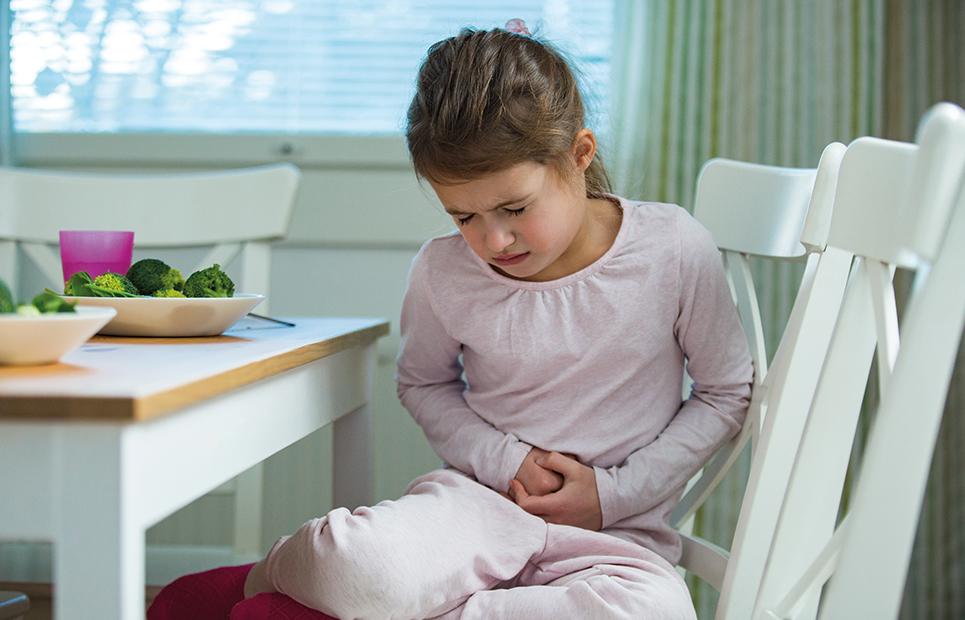 Mädchen hält sich mit schmerzverzerrtem Gesicht den Bauch