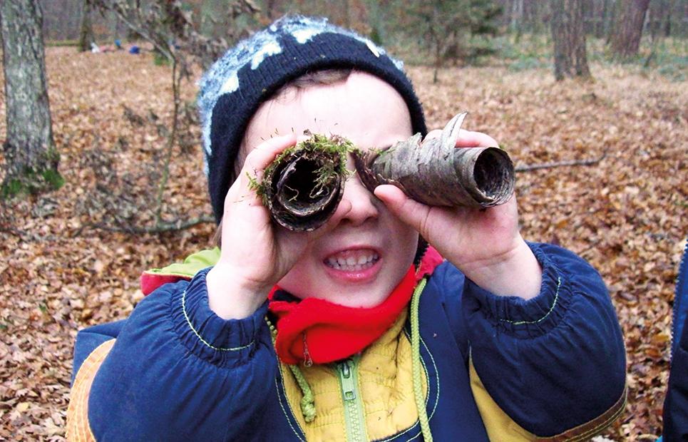 Junge schaut durch ein aus Baumrinde gebasteltes Fernglas
