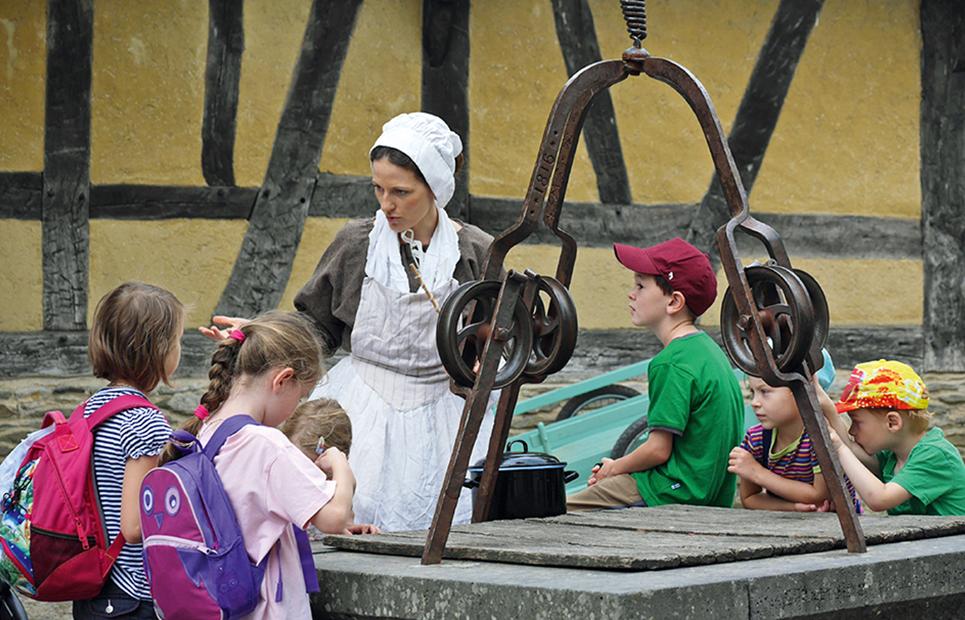 Frau in einem altertümlichen Gewand erklärt Kindern das alte Handwerk