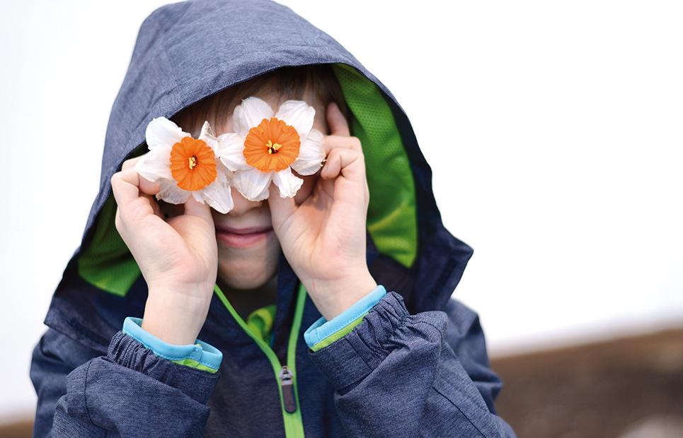 Junge hält sich zwei Narzissen-Blüten vor die Augen