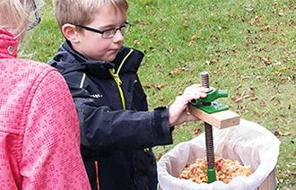 Junge an einer Apfelpresse