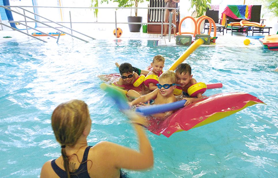 Kinder plantschen mit Luftmatratze und Schwimmnudeln in einem Schwimmbecken