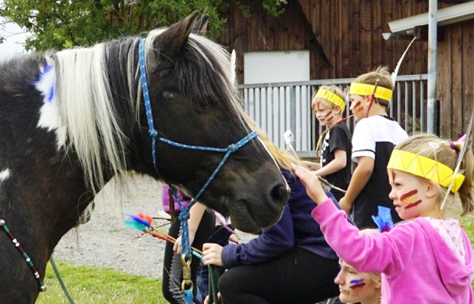 Mädchen mit Indianerverklidung streichelt ein Pony