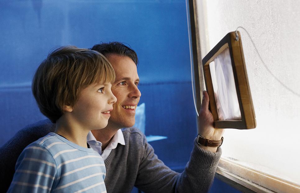 Mann mit Kind schauen durch einen Bilderrahmen
