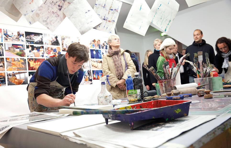 Besucher des Sinclair-Hauses beobachten einen Künstler im Atelier