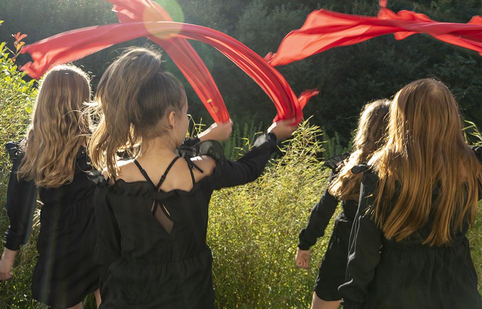 Mädchen die rote Tücher synchron durch die Luft schwingen