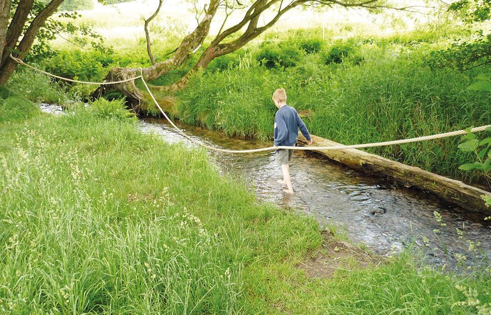 Eine Junge läuft durch den Bach Orb. Er hält sich dabei an seinem Seil fest.