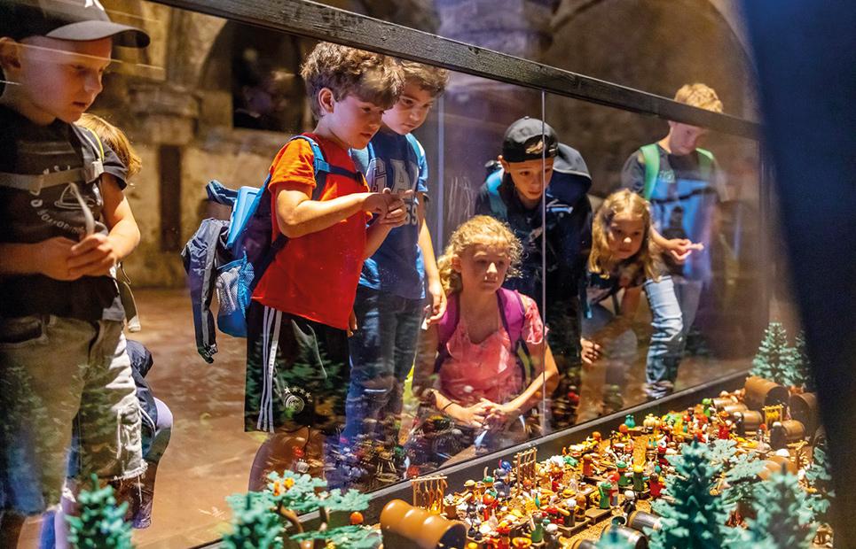 Kinder betrachten eine Ausstellungsfläche mit augebautem Playmobil
